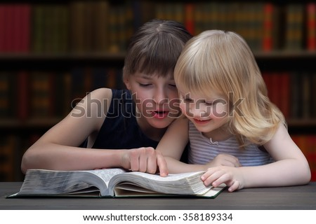 Children reading a book in the library. Two sisters, girl, reading a book. The elder sister, teenager, thumb drives along the lines of the text. The younger a girl reading a book with interest