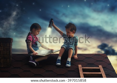 Children reading a book sitting on the roof of the house. Boy and girl reading by the light of a flashlight at night. - stock photo