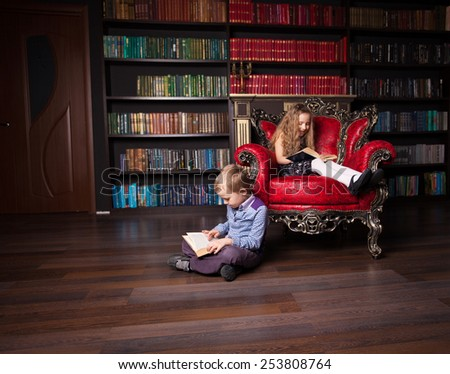 Children reading book at home. Boy and girl in library - stock photo