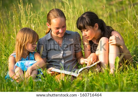 Children reading book on the park together. - stock photo