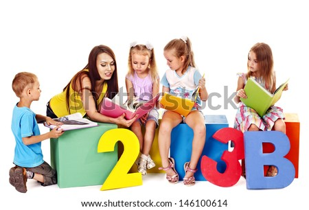 Children reading book sitting at cube. - stock photo