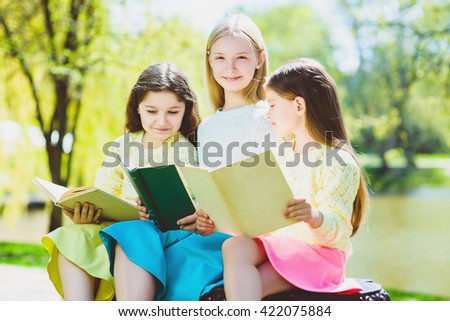Children reading books at park. Girls sitting against trees and lake outdoor - stock photo