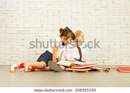 Children reading on the floor. - stock photo