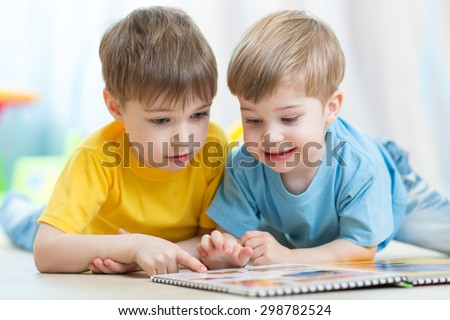 children reading together book lying on floor in nursery - stock photo