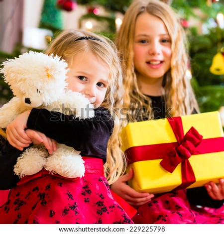 Children receiving presents on Christmas day - stock photo