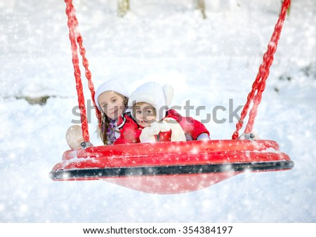 children ride on a swing in winter park