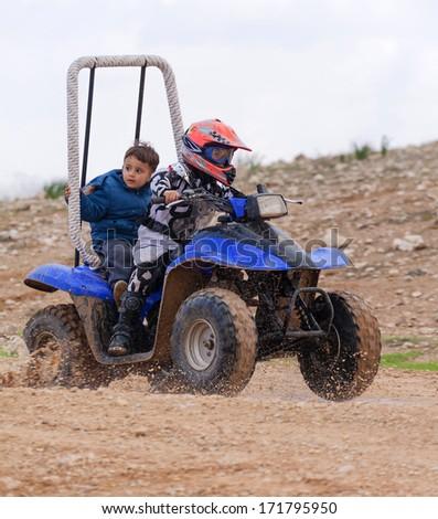 children ride on an ATV, the mud - stock photo