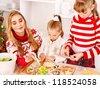 Children rolling dough in Xmas kitchen. - stock photo