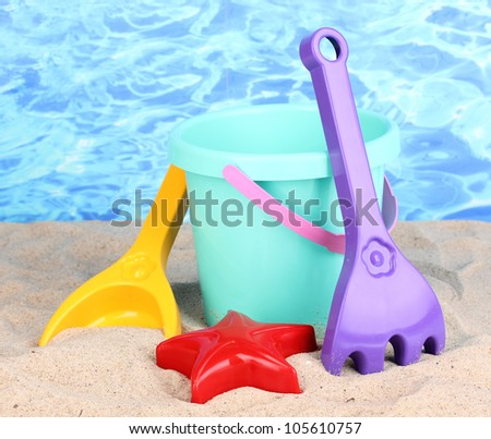 Children's beach toys on sand on water background