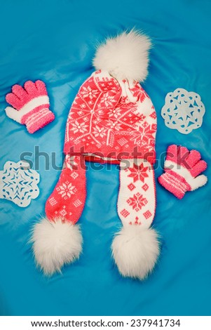 Children's cap and gloves on a blue background - stock photo