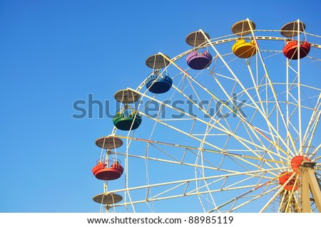 Children's carousel with colored booths against the blue sky - stock photo