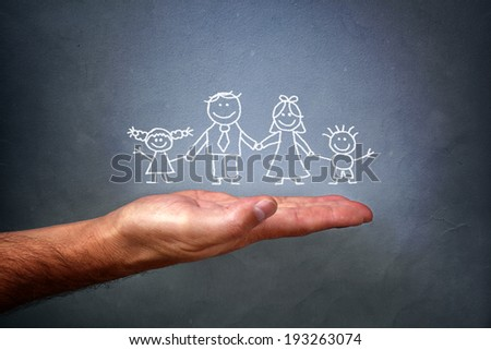 Children's chalk drawing on a blackboard of a happy family with mom, dad, son and daughter holding hands being held in the palm of a mans hand - stock photo