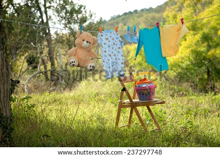 children's clothes on the clothesline in the autumn park - stock photo