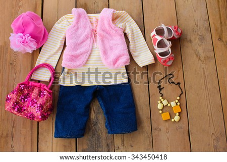Children's clothing and accessories: vest, jeans, jacket, shoes, hat and handbag on wooden background  - stock photo