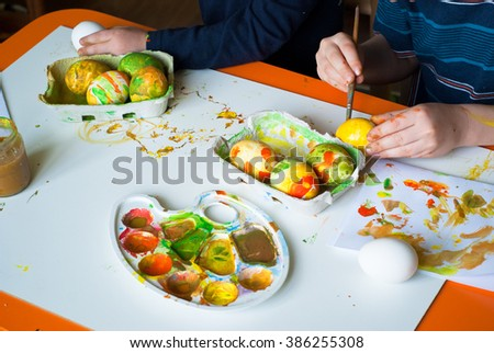 Children's creativity. Two boys painting the eggs for Easter