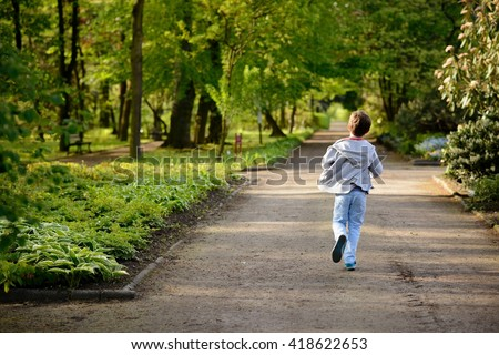 Children's Day.  Little boy running in the park. Back view