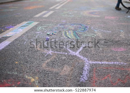 Children's drawing with chalk on a street with purple chalk