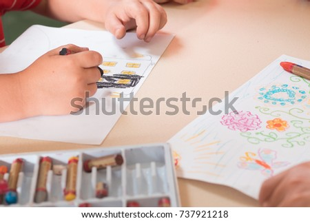 children's drawings, hands and albums with pencils on the table