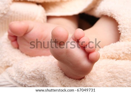 children's feet in the hands of the mother against the backdrop of a pink towel
