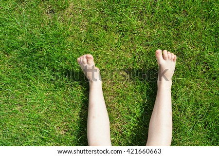 Children's feet on the green grass.