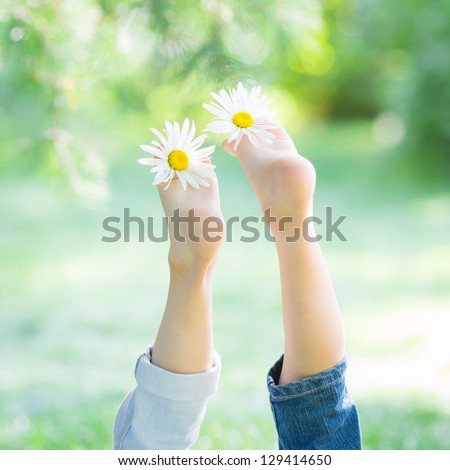 Children`s feet with flowers against green spring background. Healthy lifestyles concept - stock photo