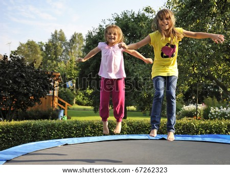 Children's fun on garden trampoline - stock photo