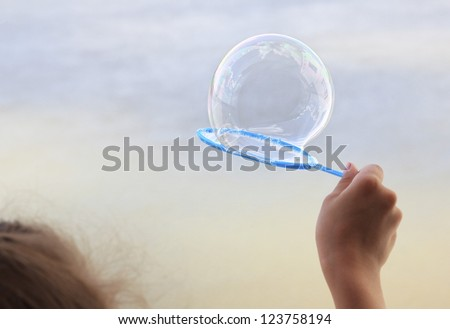 Children's hand with a soap bubble.