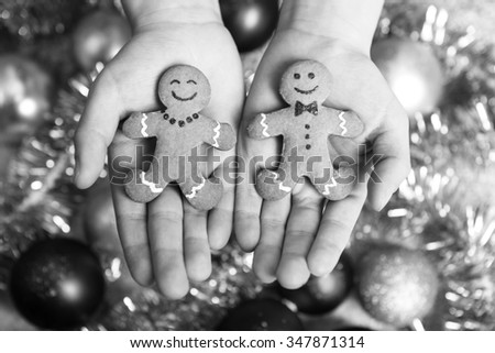 children's hands holding fresh and delicious cookies with christmas ornaments in the background - stock photo