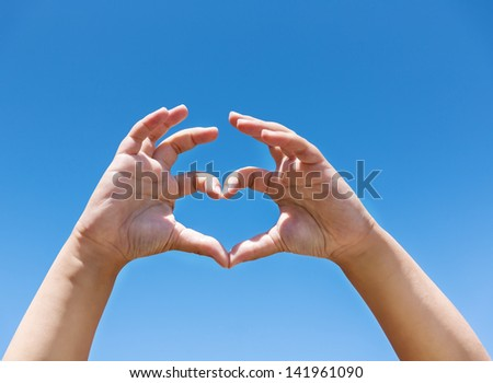 Children's hands showing the sign of heart on background the blue sky