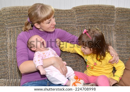 Children's jealousy. The three-year-old girl pushes away mother a hand, looking at the little sister  - stock photo