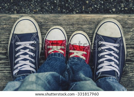 Children's legs and feet in shoes adult sneakers with each other. - stock photo