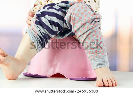 Children's legs hanging down from a chamber-pot on a green background - stock photo