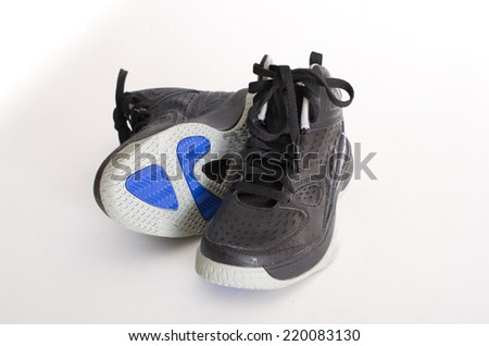 Children's modern high-top black leather and mesh basketball shoes,  sneakers showing the sole, isolated on white - stock photo