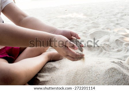 Children's play sand, Young girl molds of sand on the beach.