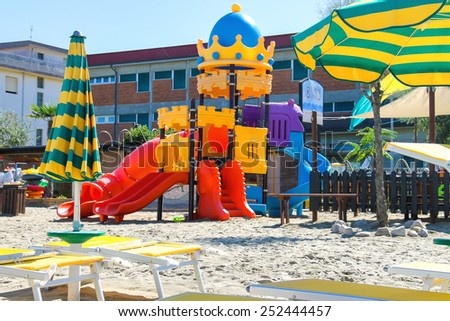 Children's playground, beach chairs and umbrellas on the beach  in the resort town Bellaria Igea Marina, Rimini, Italy
