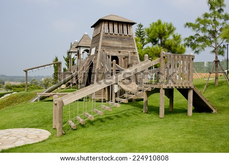 Children's Playground made from wood in park - stock photo