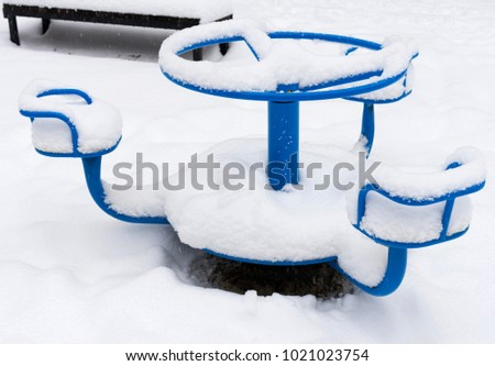 Children's playground swing covered with snow. Selective focus.