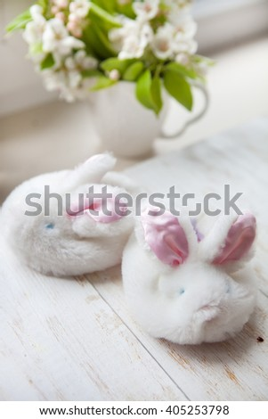 children's shoes Slippers with bunnies. cozy house. little girlie baby shoes on a wooden floor - stock photo
