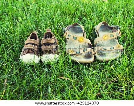 Children's shoes stands on the grass while relaxing.