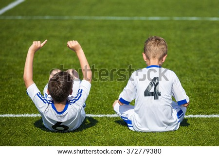 Children's soccer match. Young boys reserve soccer players sitting on a sport field and watching football match ready to play. White uniforms of soccer players with numbers on back.  - stock photo