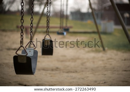 Children's swings hang empty an idle at a playground on a dull, overcast day. - stock photo