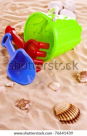 Children's toys -  bucket, spade and shovel on sand - stock photo