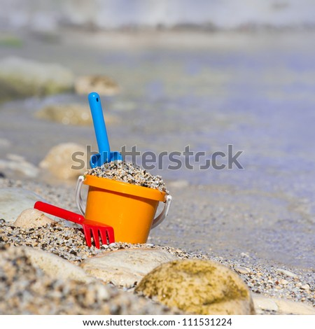 Children's toys bucket with shovels on the beach - stock photo