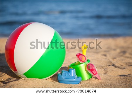 Children`s toys for sand and inflatable ball at the beach. Summer vacations concept - stock photo