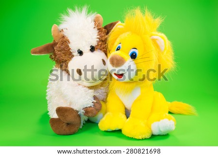 Children's toys of a bull and lion with a book on a light green background - stock photo