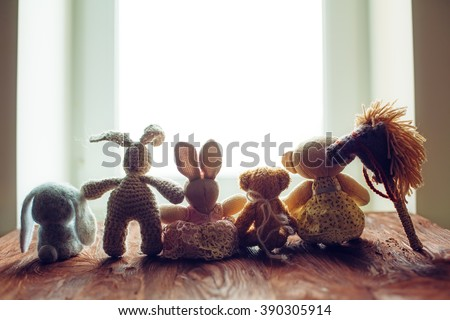 children's toys on wooden floor in front of the window - stock photo