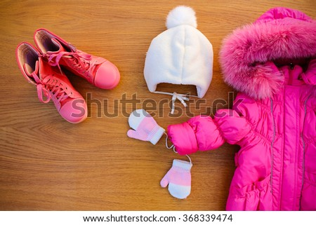 Children's winter clothes: warm pink jacket, hat, mittens, boots - stock photo