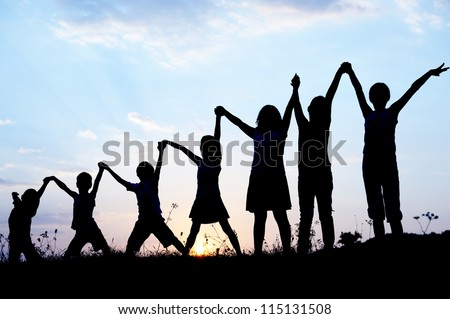 Children silhouettes holding hands up - stock photo