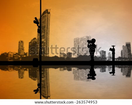 Children silhouettes take photos with a camera over blurred city Scape