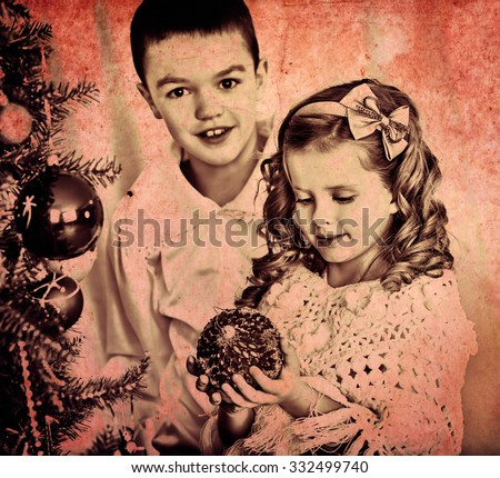 Children sister and brother decorate on Christmas tree. Black and white retro. - stock photo